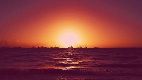 Ηλιοβασίλεμα τέχνης στην παραλία Κόκκινο ηλιοβασίλεμα πέρα από τη θάλασσα με τα γιοτ και τις βάρκες φιλμ μικρού μήκους