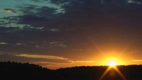 Ηλιοβασίλεμα, χρυσός ήλιος πέρα από τα δασικά, μαύρα σύννεφα φιλμ μικρού μήκους