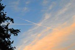 Ηλιοβασίλεμα-χρωματισμένα σύννεφα, ίχνη ενός πετώντας πάνω από αεροπλάνου στον ουρανό στοκ φωτογραφίες
