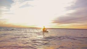 Ηλιοβασίλεμα waterscape με μια κυρία που επιπλέει σε ένα paddleboard καρπός ρολογιών χαλάρωσης τσεπών χεριών έννοιας απόθεμα βίντεο