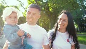 Ηλιοφάνεια στην ευτυχή οικογένεια με το περπάτημα κοριτσάκι στο θερινό πάρκο απόθεμα βίντεο
