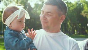 Ηλιοφάνεια στον ευτυχή πατέρα που κρατά το κοριτσάκι του περπατώντας στο θερινό πάρκο απόθεμα βίντεο