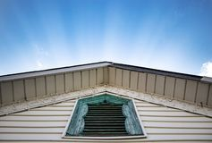 Ηλιοφώτιστες ακτίνες που λάμπουν πίσω από την οξυνμένη στέγη με το αγροτικό μπλε παράθυρο στοκ εικόνα
