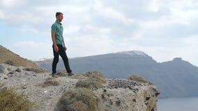 Ηλιοφώτιστη θάλασσα επί της ουσίας του απότομου απότομου βράχου, στάση τύπων που εξετάζει το τοπίο από την κορυφή απόθεμα βίντεο