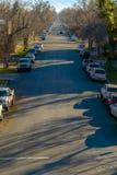 Ηλιοφώτιστος δρόμος που ευθυγραμμίζεται με τα οχήματα και τα δέντρα σε Provo στοκ φωτογραφίες