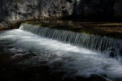 Ηλιοφώτιστος καταρράκτης με το γλυκό νερό ενός αλπικού ποταμού στοκ φωτογραφία