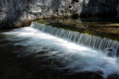Ηλιοφώτιστος καταρράκτης με το γλυκό νερό ενός αλπικού ποταμού στοκ εικόνα