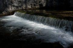 Ηλιοφώτιστος καταρράκτης με το γλυκό νερό ενός αλπικού ποταμού στοκ εικόνες