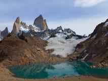 Ηλιόλουστα βουνά με την τυρκουάζ λίμνη Χιόνι που βρίσκεται στην κλίση του βουνού στοκ εικόνες