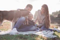 ηλιόλουστες εικόνες ενός ευτυχούς παντρεμένου ζευγαριού με ένα σκυλί και ένα παιδί στοκ εικόνες