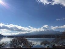 Ηλιόλουστη άποψη ημέρας της ΑΜ Φούτζι με το σαφή μπλε ουρανό, τα σύννεφα και την ομαλή επιφάνεια λιμνών το χειμώνα, Kawaguchiko,  Στοκ εικόνα με δικαίωμα ελεύθερης χρήσης