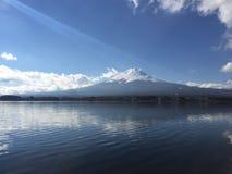 Ηλιόλουστη άποψη ημέρας της ΑΜ Φούτζι με το σαφή μπλε ουρανό, τα σύννεφα και την ομαλή επιφάνεια λιμνών, Kawaguchiko, Yamanashi,  Στοκ εικόνα με δικαίωμα ελεύθερης χρήσης