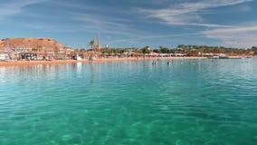 Ηλιόλουστη ημέρα και παραλία σε ένα τροπικό θέρετρο στο οποίο οι παραγνωρισμένοι τουρίστες κάνουν ηλιοθεραπεία και κολυμπούν στη  απόθεμα βίντεο