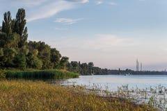 Ηλιόλουστη ημέρα σε έναν ήρεμο ποταμό με τα bulrushes το καλοκαίρι Nova Kakhovka, Ουκρανία Υψηλής τάσεως ηλεκτροφόρα καλώδια στο  στοκ εικόνες