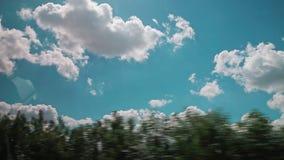 Ηλιόλουστος θερινός καιρός, όμορφα σύννεφα, επαρχία μέσω του παραθύρου ενός αυτοκινήτου φιλμ μικρού μήκους