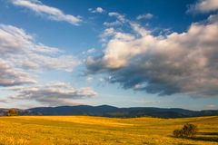 Ηλιόλουστο τοπίο με τα βουνά και μπλε ουρανός με τα σύννεφα Στοκ Φωτογραφία
