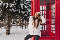 Ηλιόλουστο χειμερινό πρωί, καλή διάθεση της γοητείας του κοριτσιού στα θερμά ενδύματα που απολαμβάνουν κοντά στο κόκκινο τηλεφωνι στοκ εικόνα