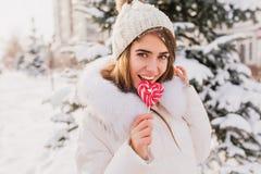 Ηλιόλουστο χειμερινό πρωί στην οδό της γοητείας της νέας γυναίκας που γλείφει το ρόδινο lollypop Ευτυχής χρόνος, θετικές συγκινήσ στοκ φωτογραφίες με δικαίωμα ελεύθερης χρήσης