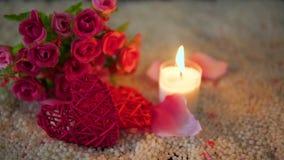 Ημέρα βαλεντίνων με την καρδιά διακοσμήσεων μήκους σε πόδηα, το κάψιμο κεριών και την ανθοδέσμη απόθεμα βίντεο