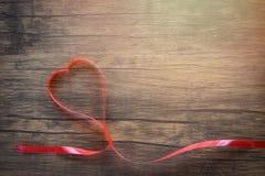 Ημέρα βαλεντίνων με την κόκκινη καρδιά κορδελλών στην ξύλινη τοπ άποψη υποβάθρου στοκ εικόνα