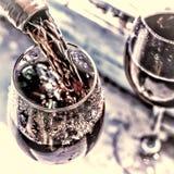 Ημέρα βαλεντίνων ` s, ημερομηνία, αγάπη, εορτασμός χύνοντας κόκκινο κρασί Κρασί σε ένα γυαλί, εκλεκτική εστίαση, θαμπάδα κινήσεων Στοκ Φωτογραφία