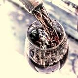 Ημέρα βαλεντίνων ` s, ημερομηνία, αγάπη, εορτασμός χύνοντας κόκκινο κρασί Κρασί σε ένα γυαλί, εκλεκτική εστίαση, θαμπάδα κινήσεων Στοκ Εικόνες