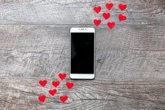 Ημέρα βαλεντίνων ` s, τηλέφωνο στο ξύλινο γκρίζο υπόβαθρο, με τις κόκκινες καρδιές, η αγάπη, η σύνδεση μεταξύ των δύο, κατάλληλος Στοκ φωτογραφία με δικαίωμα ελεύθερης χρήσης