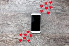 Ημέρα βαλεντίνων ` s, τηλέφωνο στο ξύλινο γκρίζο υπόβαθρο, με τις κόκκινες καρδιές, η αγάπη, η σύνδεση μεταξύ των δύο, κατάλληλος Στοκ Εικόνες