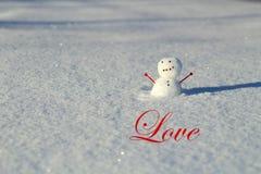 Ημέρα βαλεντίνου: Λίγος χιονάνθρωπος στο χιόνι έξω με το βραχίονα καρδιών στοκ εικόνες με δικαίωμα ελεύθερης χρήσης