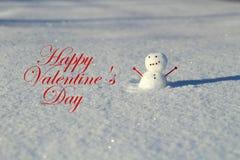 Ημέρα βαλεντίνου: Λίγος χιονάνθρωπος στο χιόνι έξω με το βραχίονα καρδιών στοκ εικόνες