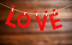 Ημέρα βαλεντίνων ` s υποβάθρου δύο κόκκινες καρδιές και αγάπη λέξης σε ξύλινο Στοκ Εικόνες