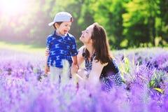 Ημέρα γυναικών Ευτυχές mom με το χαριτωμένο γιο lavender στο υπόβαθρο όμορφη γυναίκα στοκ εικόνα