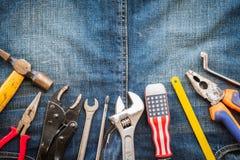 Ημέρα εργασίας, την 1η Μαΐου Πολλά πρακτικά εργαλεία με το κενό διάστημα στα τζιν Στοκ Εικόνες