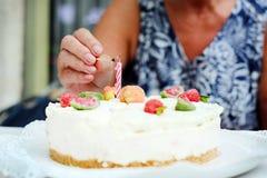 Ημέρα μητέρων, γενέθλια εορτασμού, που ανάβει ένα κερί σε ένα κέικ Στοκ Εικόνα