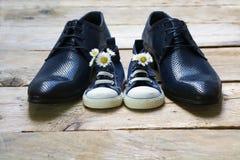 Ημέρα πατέρα, πάνινα παπούτσια παιδιών με μια ανθοδέσμη των μαργαριτών που στέκονται το β Στοκ Εικόνες