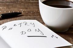 Ημέρα ποίησης κειμένων σε ένα σημειωματάριο και ένα φλιτζάνι του καφέ στοκ φωτογραφία με δικαίωμα ελεύθερης χρήσης