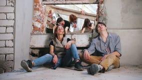 Ημέρα της Κρίσεως, αποκάλυψη Δύο επέζησαν των ανθρώπων που κάθονται στο πάτωμα και το καπνίζοντας τσιγάρο Zombies σε ένα υπόβαθρο απόθεμα βίντεο