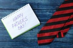 Ημέρα του ευτυχούς πατέρα Κείμενο στο σημειωματάριο και δεσμός σε έναν μπλε ξύλινο πίνακα διακοπές ατόμων r στοκ φωτογραφία με δικαίωμα ελεύθερης χρήσης