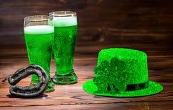 Ημέρα του ST Patricks με τα ποτήρια της πράσινης μπύρας, τριφύλλι φύλλων, ελαφρύ λ στοκ εικόνες