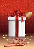 Ημέρα των ευτυχών γυναικών Κιβώτιο δώρων σε ένα κόκκινο υπόβαθρο με τις καρδιές Στοκ εικόνες με δικαίωμα ελεύθερης χρήσης