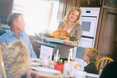 Ημέρα των ευχαριστιών: Η μητέρα φέρνει την ψημένη Τουρκία στον πίνακα Στοκ Εικόνα