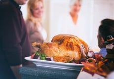 Ημέρα των ευχαριστιών: Η ψημένη Τουρκία στηρίζεται στο μετρητή ενώ η οικογένεια μιλά Στοκ φωτογραφία με δικαίωμα ελεύθερης χρήσης