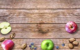 Ημέρα των ευχαριστιών με τα μήλα, τα ξύλα καρυδιάς και τα μούρα σε ένα παλαιό ξύλινο υπόβαθρο Ημέρα των ευχαριστιών με τα εποχιακ Στοκ Φωτογραφίες