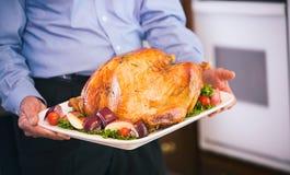 Ημέρα των ευχαριστιών: Φέρνοντας ψητό Τουρκία παππούδων στον πίνακα γευμάτων Στοκ Εικόνες