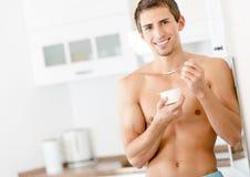 Ημίγυμνος νεαρός άνδρας που τρώει το γιαούρτι Στοκ φωτογραφία με δικαίωμα ελεύθερης χρήσης