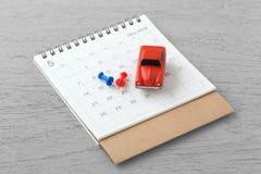Ημερολόγιο και κόκκινα αυτοκίνητα παιχνιδιών στοκ φωτογραφία
