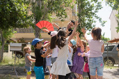 Ημερομηνία: 17/5/2015 Θέση: Πάρκο στην Αθήνα Μαγικός παρουσιάστε με το Tristan Ευτυχή παιδιά που προσπαθούν να πιάσει το κομφετί Στοκ Εικόνα