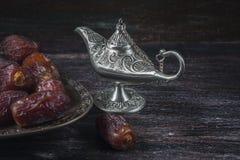 Ημερομηνίες και ασημένιος λαμπτήρας aladdin ` s σε ένα σκοτεινό ξύλινο υπόβαθρο Έννοια Ramadan Στοκ Εικόνα