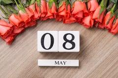 Ημερολόγιο μορφής κύβων για την 8η Μαΐου στον ξύλινο πίνακα με τα τριαντάφυλλα Στοκ Εικόνες