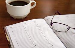 Ημερολόγιο σε έναν ξύλινο πίνακα, δίπλα στα γυαλιά και ένα φλιτζάνι του καφέ Στοκ Φωτογραφία